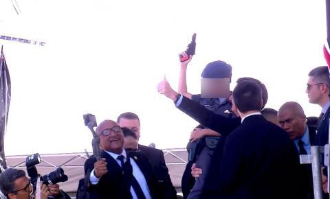 Criança com farda da PM e arma de brinquedo na mão posa para fotos com Bolsonaro